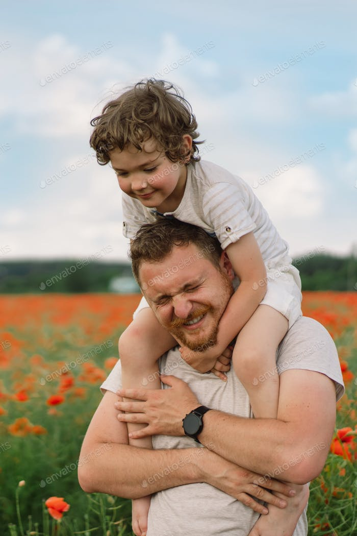 Little boy and father are playing in a beautiful field of red poppies.