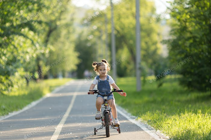 Little girl riding a bicycle in the city park