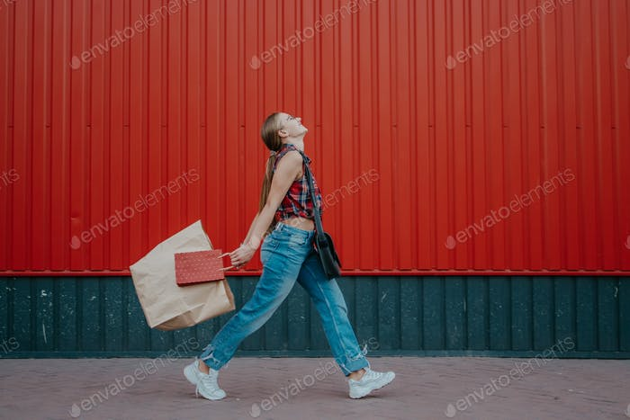 Shopping, sale concept. Happy young woman walking and holding shopping bags on red wall background o