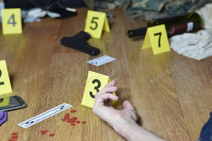 Hand of dead victim surrounded by evidence markers and objects on floor of residential apartment