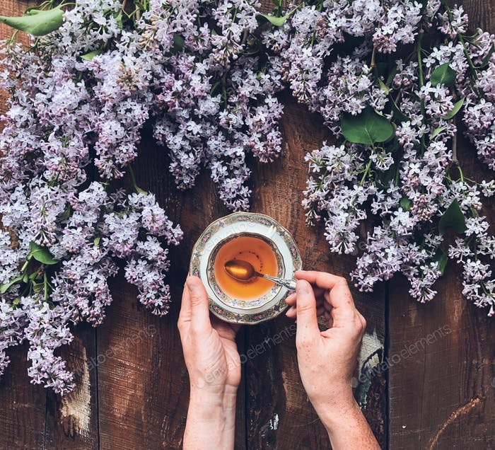 Overhead shot of woman's hands holding a pretty tea cup surrounded by fresh lilac flowers on a