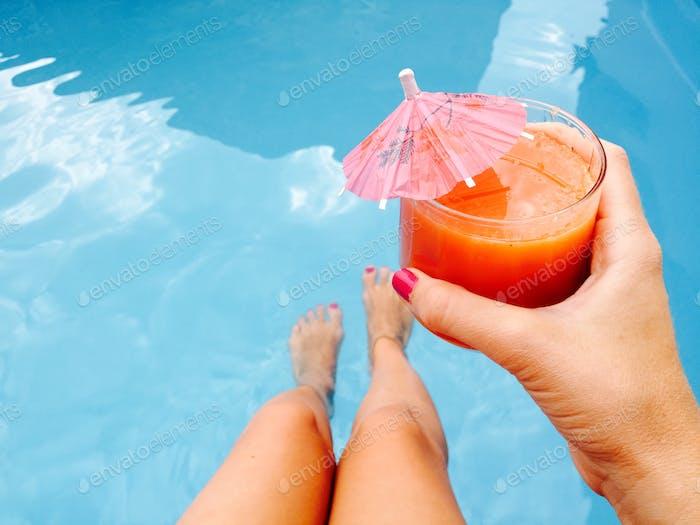 Frau Hand mit rosa Nagellack hält Glas Orangensaft mit Regenschirm über den Pool blau wate