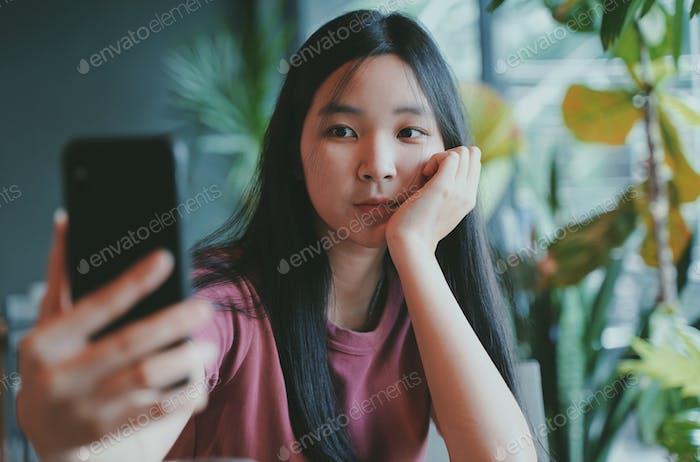 Young asian woman taking selfie