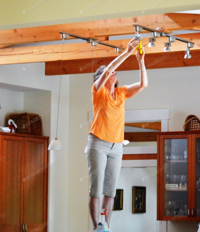 A woman dusting a light fixture.