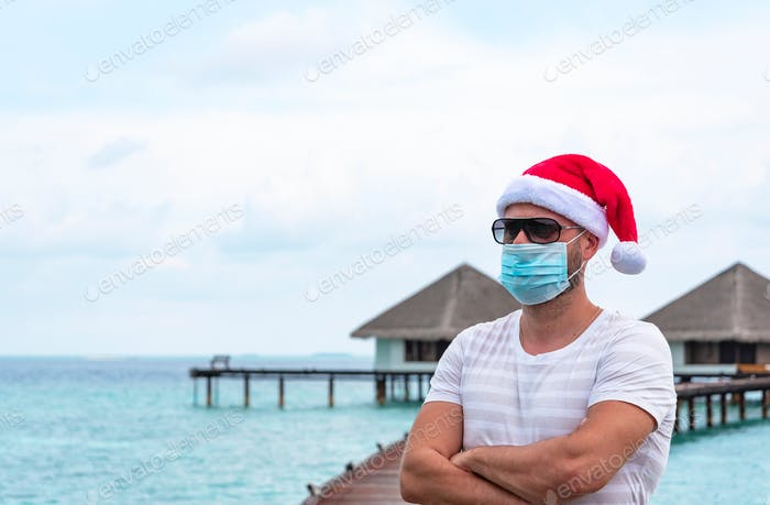 a young man wearing a protective face mask and Santa hat stands on a pier near water villas