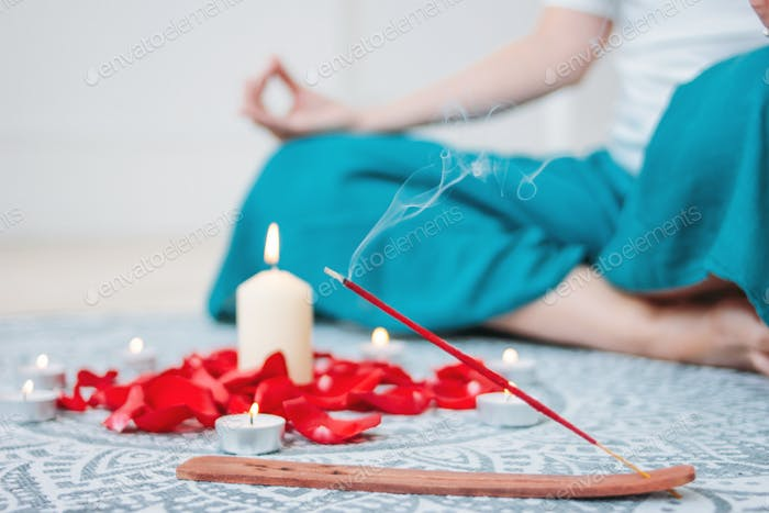 Burning incense red stick on candles background and woman practicing yoga