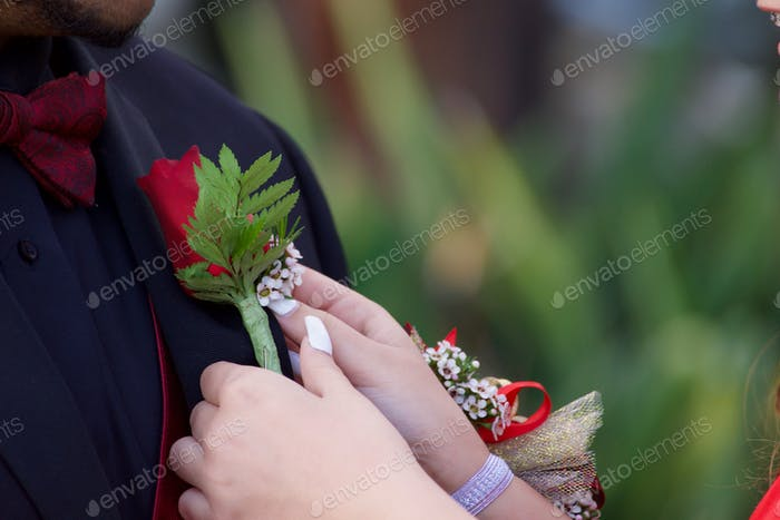 NOMINATED A woman pinning a red rose boutonniere on her date's lapel