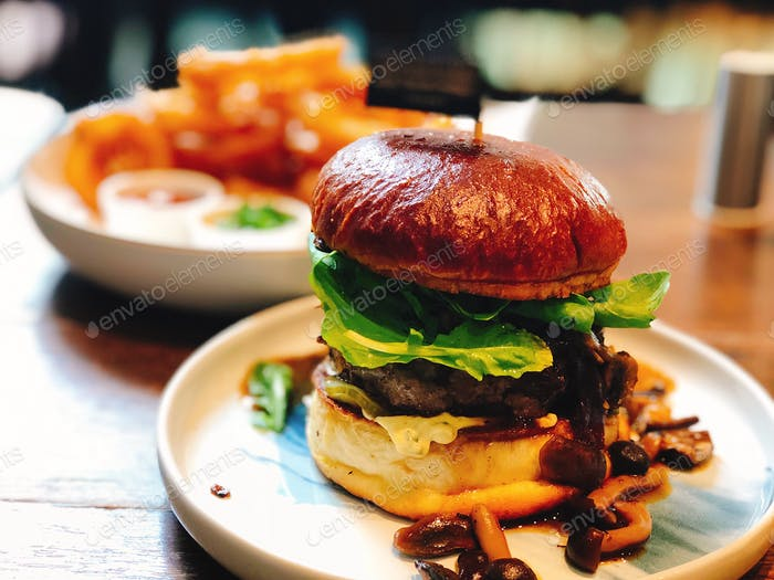 ✨🏆SIGNATURE COLLECTION🏆✨  Mushroom and beef burger 🍔 with fried onion rings in the background. Food