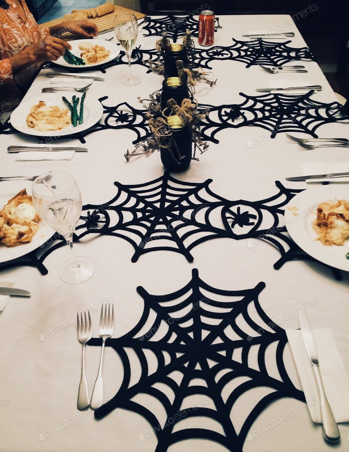 Halloween celebration dinner table decorated with spiderwebs place mats.