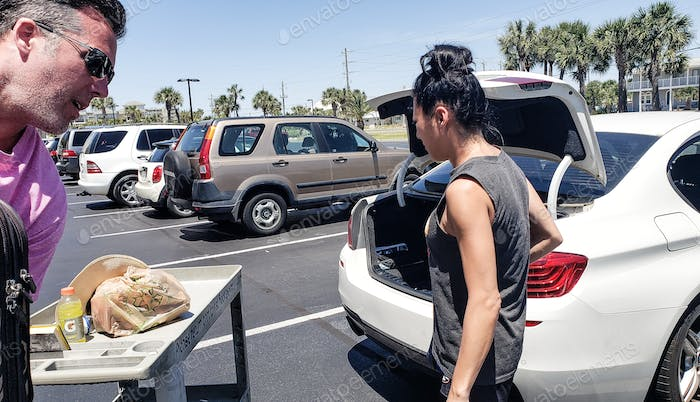 Generation X couple packing their luggage in the trunk of their car after visiting parents and ready