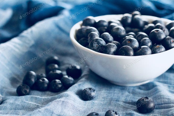 (nominated) Blueberries in a white bowl and scattered on gradated blue fabric