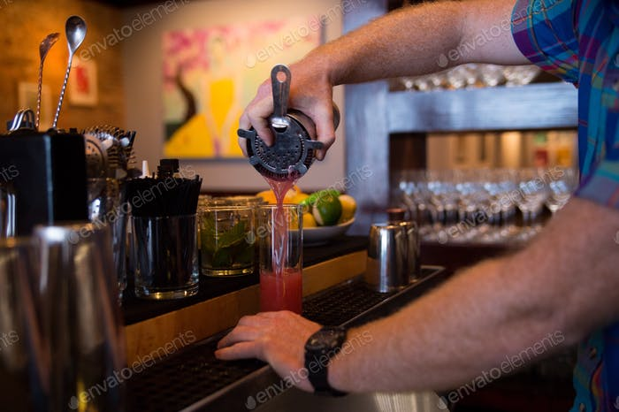 Bartender pouring pink mix drink into glass.