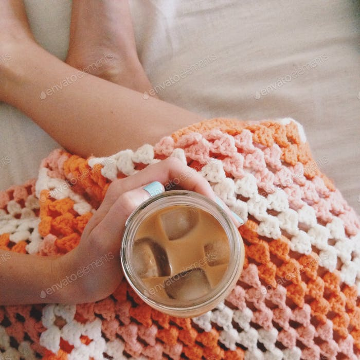 Iced coffee with crocheted blanket.