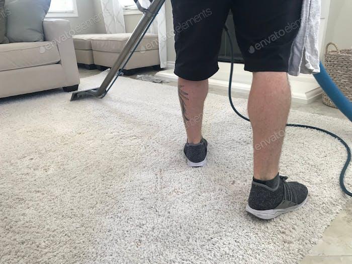 Ein Mann shampooniert einen weißen Teppich
