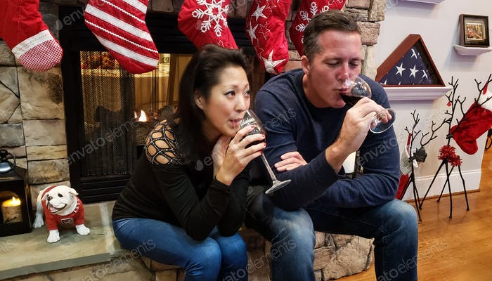 Millenial couple sitting on fireplace at family get together drinking red wine...