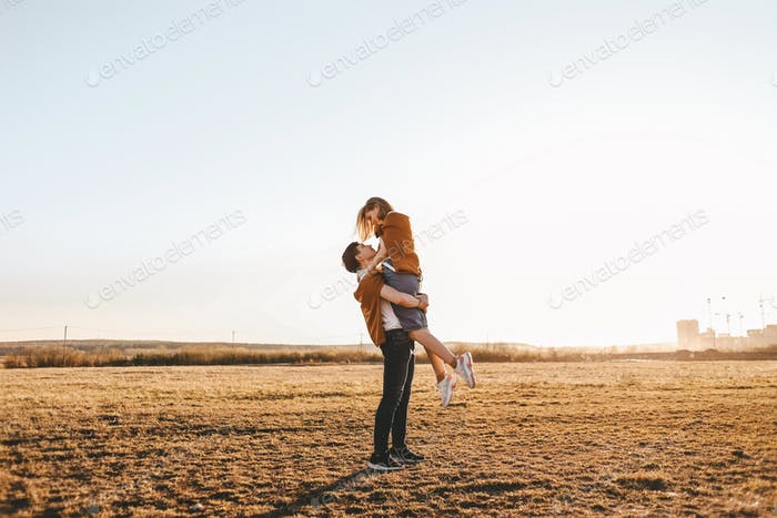 couple of lovers kissing and hugging outdoors at sunset