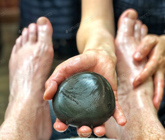 Beauty Spa Woman holds therapeutic traditional round black pumice stone as she massages relaxed