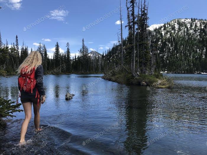 Mädchen zu Fuß in einem flachen See zu einer Insel. tief in den Bergen.
