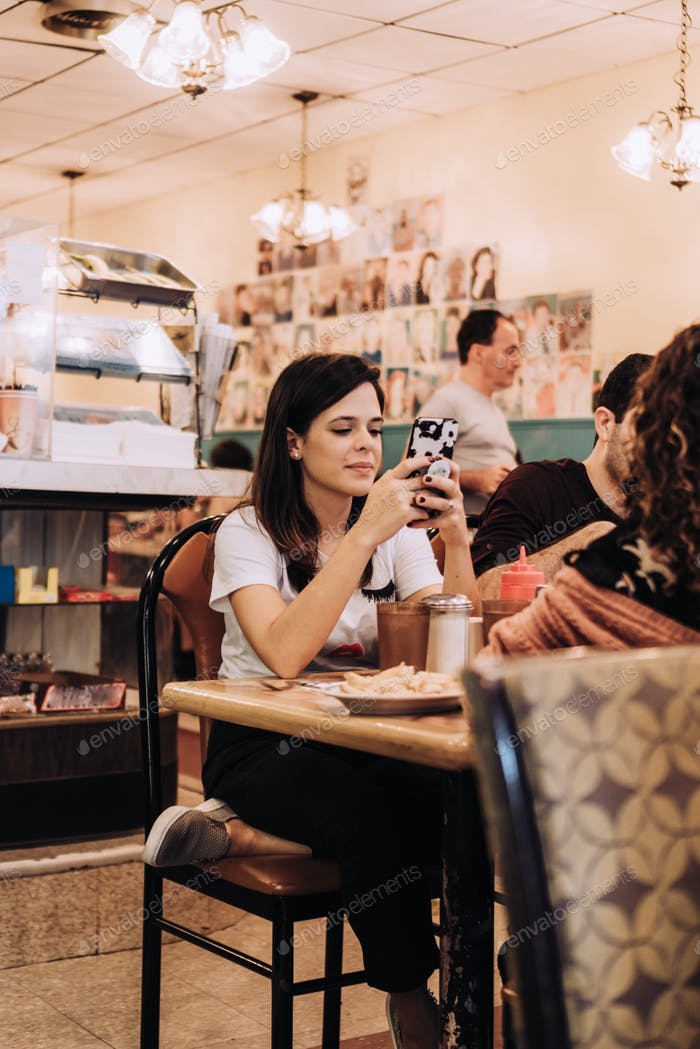 Woman using mobile in diner