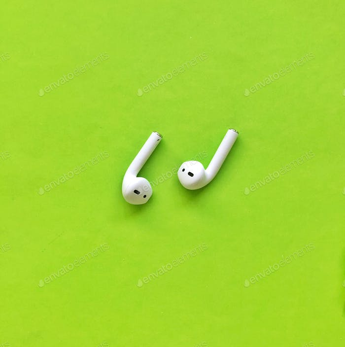 Earphones on bright green bold background