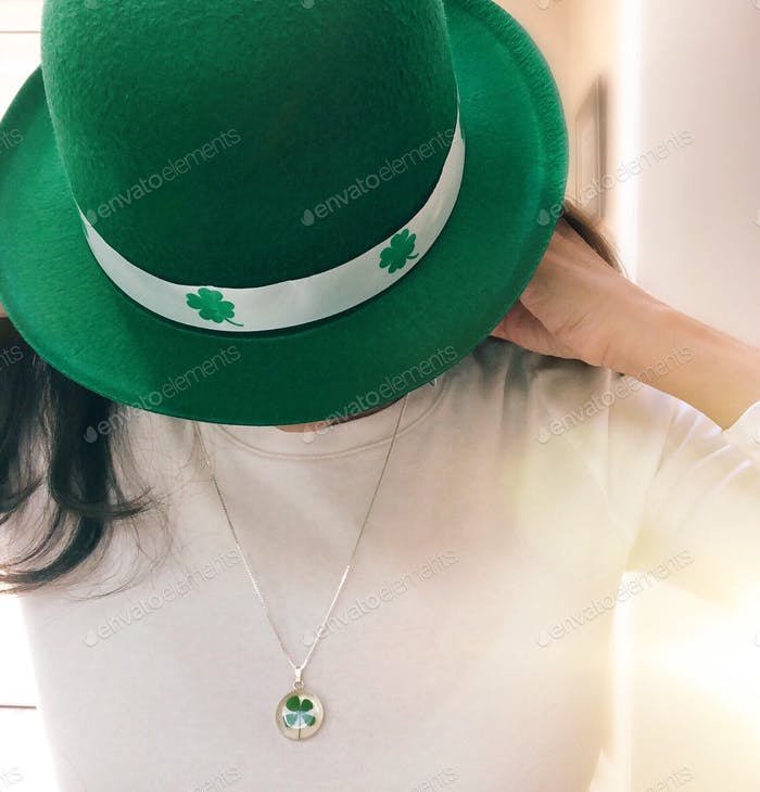 Woman getting ready & putting her shamrock necklace on for a fun St