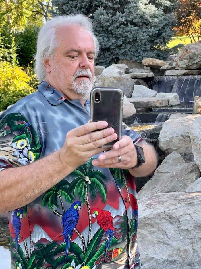 Man in Hawaiian shirt in beautifully landscaped garden taking selfie.