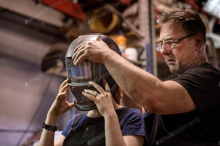 ↟ Daughter helps her father by working in his auto repair shop. Family business