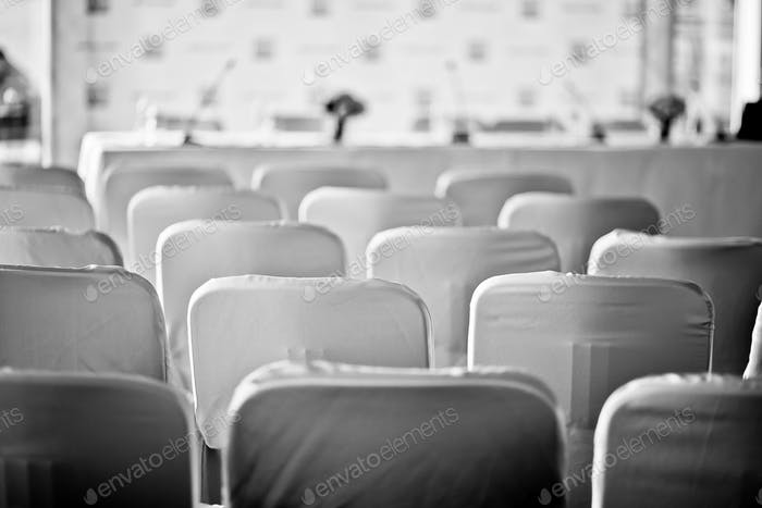 Press conference. Black and white. Chairs. Conference. Official event.