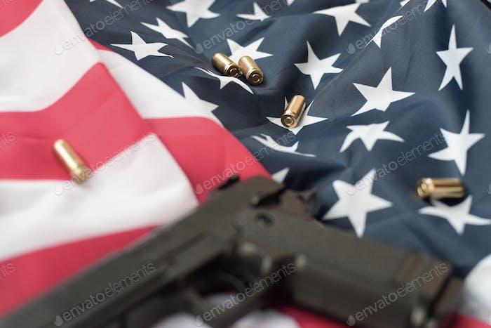 9mm bullets and pistol lie on folded United States flag
