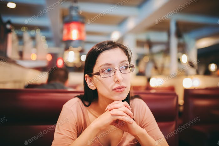 Young millennial woman deep in thought at a restaurant