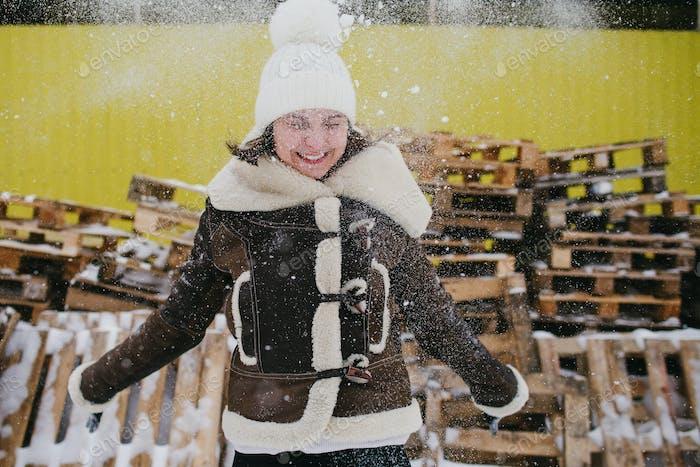 Junges Mädchen, das mit Schnee spielt. Frohe Winterzeit
