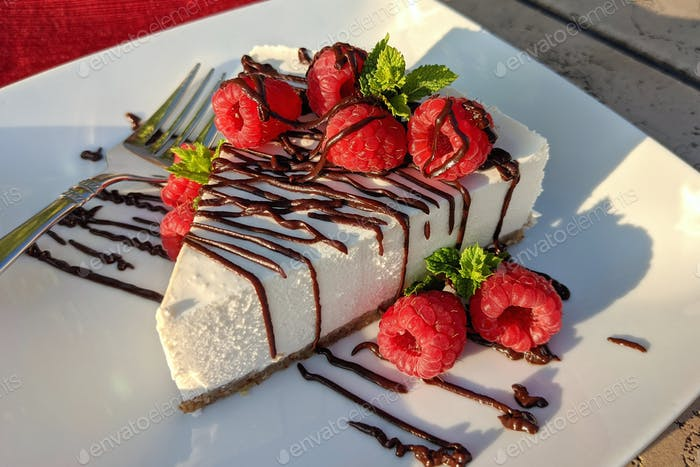 Keto cheesecake topped with raspberries, keto-friendly chocolate fudge sauce and mint for dessert