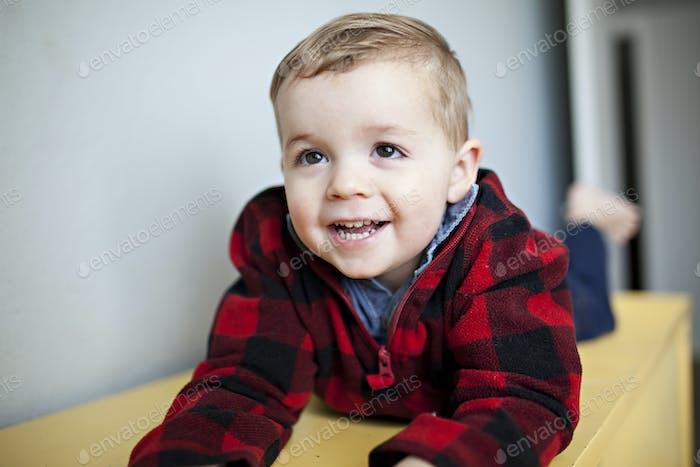 toddler boy laughing in a lumberjack sweater