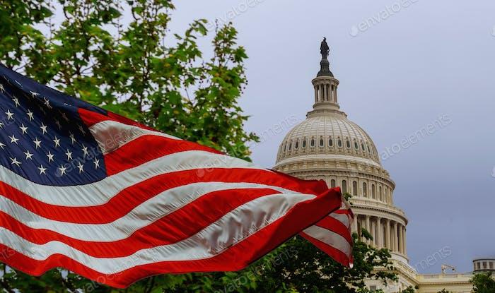 El edificio del Capitolio de los Estados Unidos con una bandera estadounidense ondeante superpuesta en el cielo Capitol Hill en