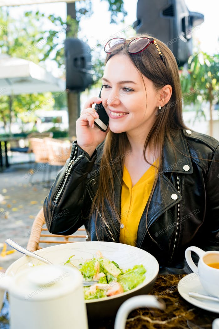 Portrait of cheerful brunette woman in casual clothes calling on smartphone while sitting in cafe ou