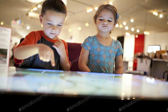 Дети с помощью гигантского сенсорного экрана