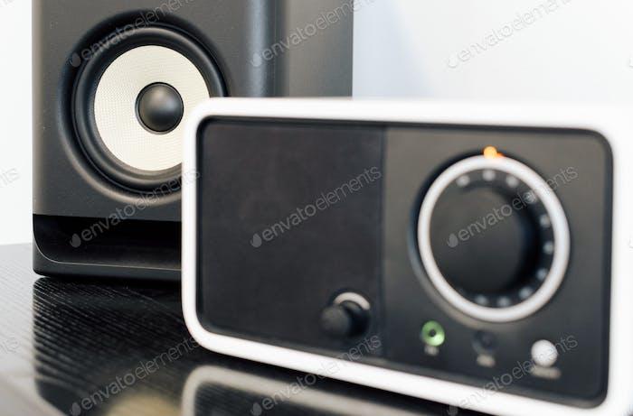 Close-up selektives Fokusbild eines Audiogeräts mit UKW-Tuner und Lautsprecher auf dem Tisch.