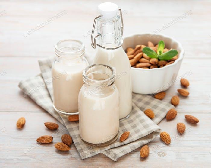 Flaschen mit Mandelmilch und Mandeln auf dem Tisch