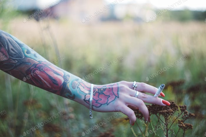 NOMINATED!!⚡⚡girl with a tattooed forearm and a cigarette walking in the autumn field, close up hand