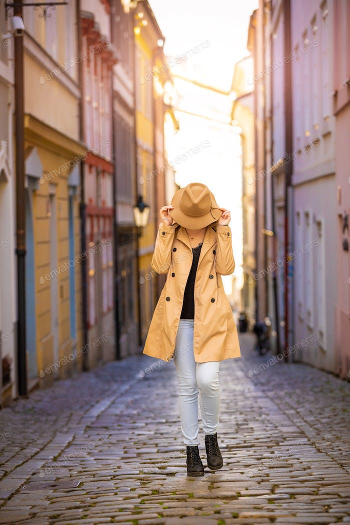 Mädchen in einem beigen Hut und Mantel in der engen Straße von Prag Stadt, Tschechische Republik
