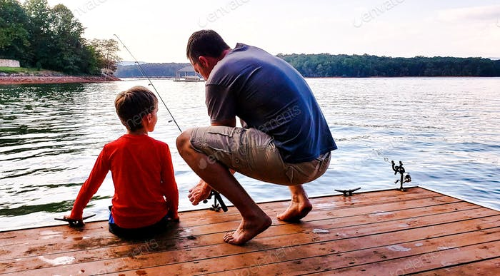 Uncle helping nephew learn to fish at the lake on a dock trying to bait the hook with mountains in b
