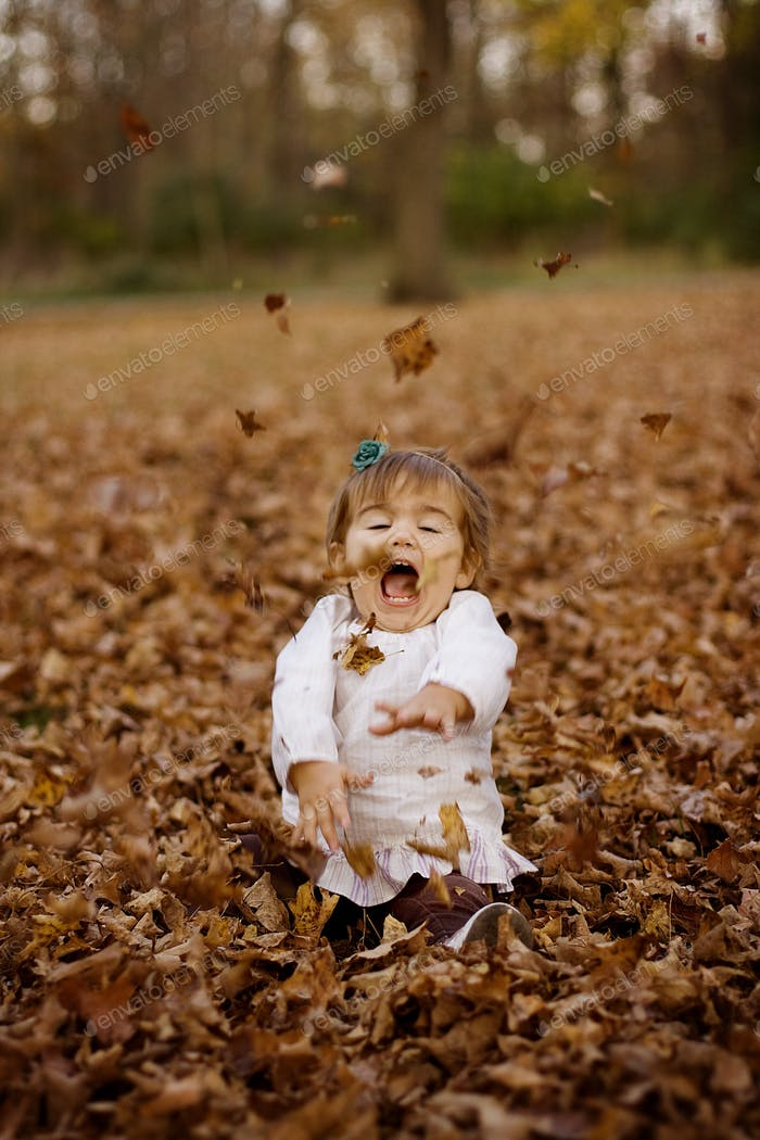 Toddler in a pile of leaves
