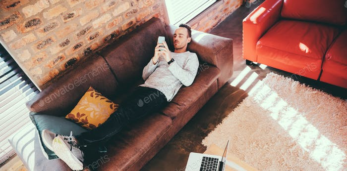 Young male adult laying comfy on couch browsing with his mobile device at modern home