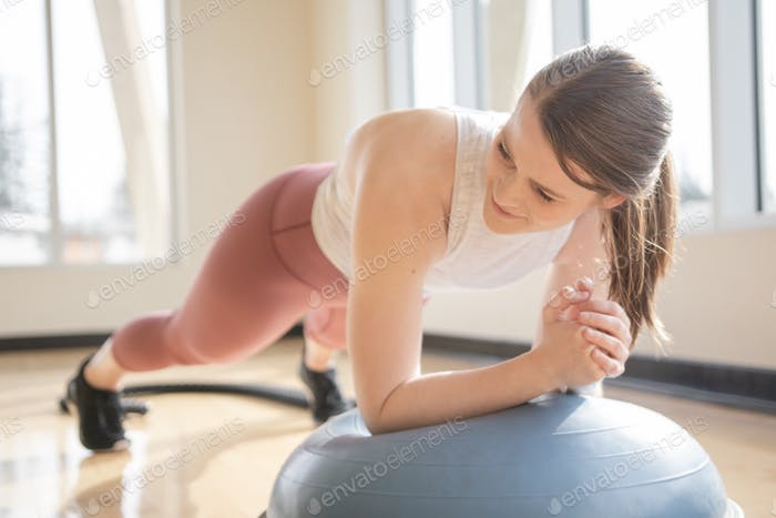 Woman doing plank exercises in a brightly lit gym