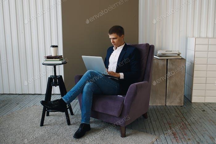 человек фрилансер работает на ноутбуке с помощью телефона смотрит на ноутбук думает, что парень деловой костюм