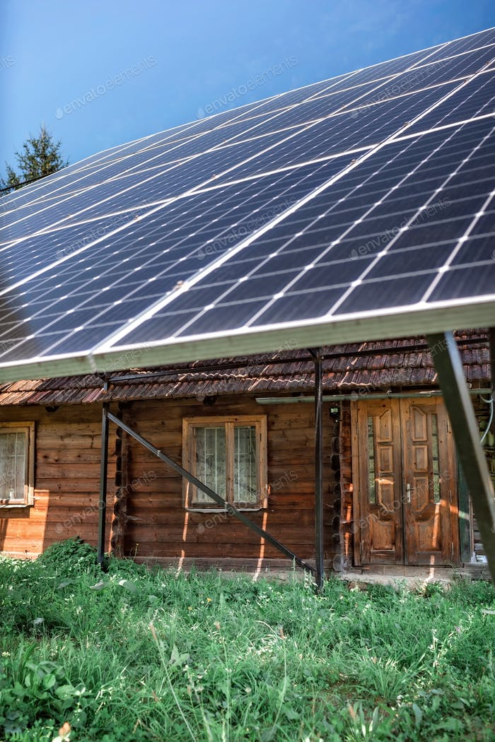 A solar panel on the roof on old wooden house at mountain countryside, green energy