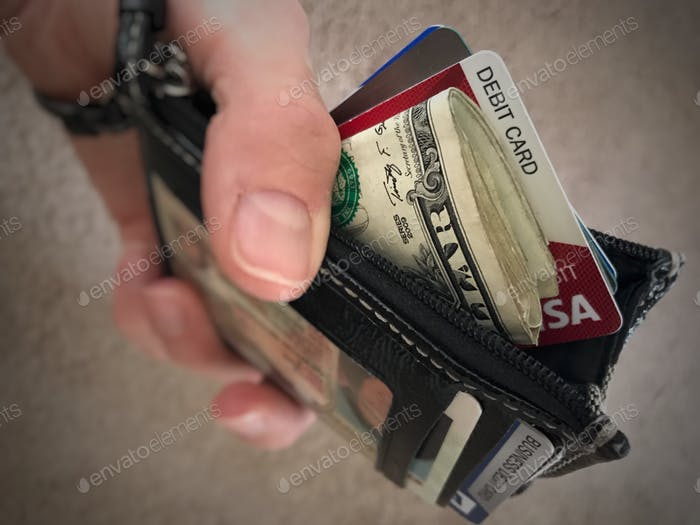 Monedero en la mano con efectivo y tarjeta de débito