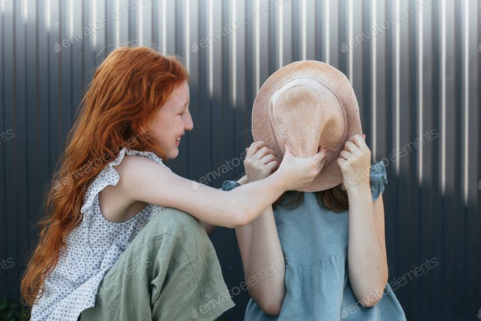 Red-haired girl covers her friend's face with a Panama hat.
