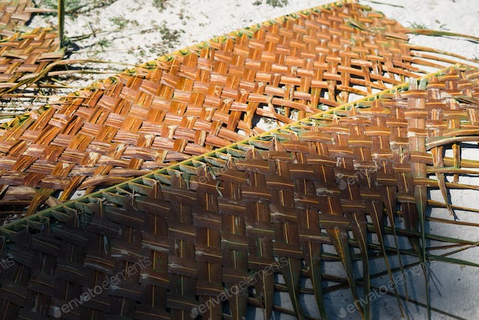 weaved leaves gor making walls and rooftop of a house lying on the ground
