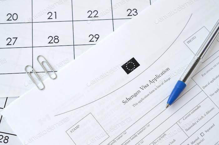 Formulario de solicitud de visado Schengen y bolígrafo azul sobre papel página de calendario de cerca